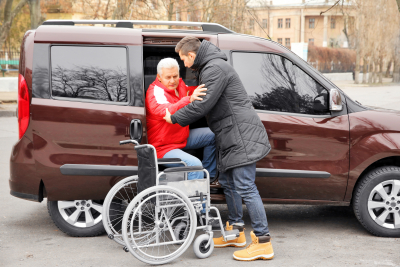 caregiver helping a senior get on his wheelchair