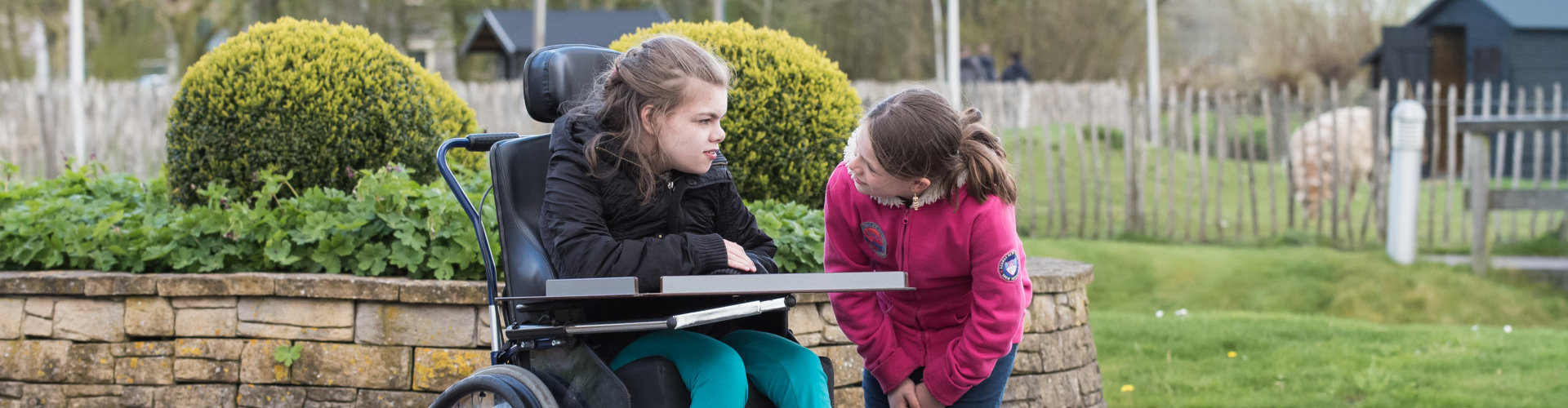 young girl talking to another girl on a wheelchair