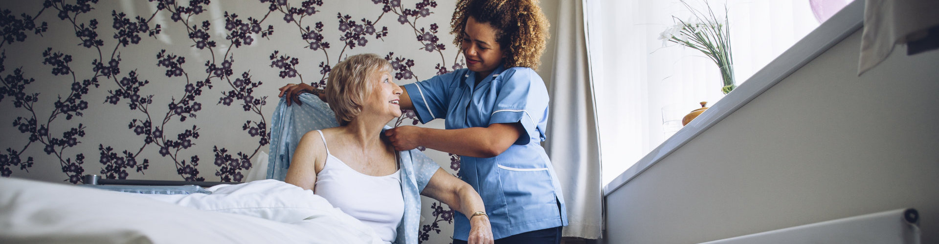 caregiver helping a senior woman dress up