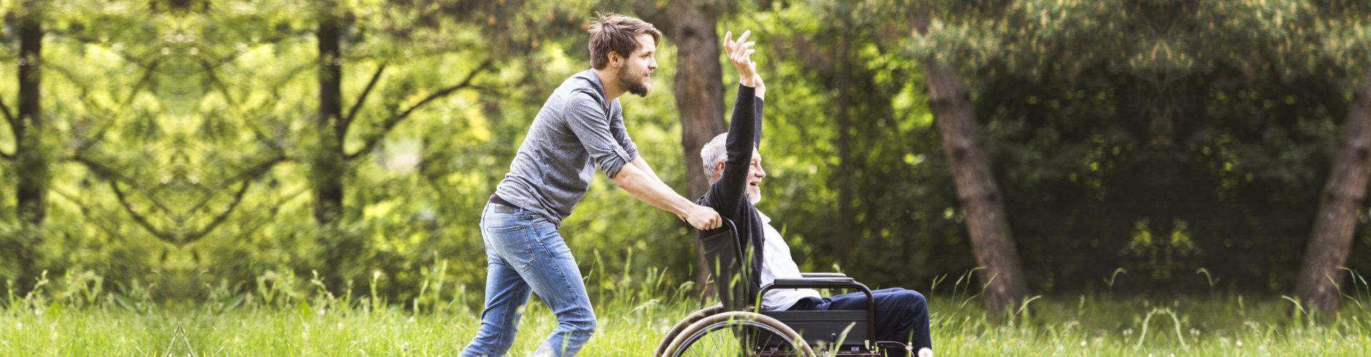senior man on a wheelchair having fun with his caregiver