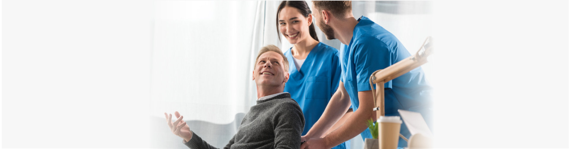 smiling doctors and patient on wheelchair talking